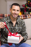 Happy man opening a gift on christmas day
