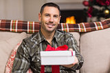 Smiling man offering gift on christmas day