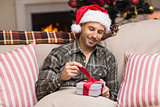 Smiling man in santa hat opening a gift