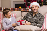 Son giving father a christmas gift on the couch