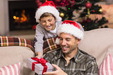 Son offering father a christmas gift on the couch