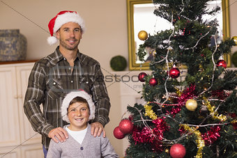 Dad and son posing near the christmas tree