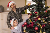 Smiling son and dad decorating the christmas tree