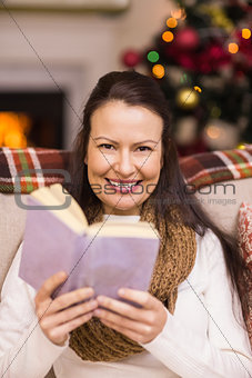 Smiling brunette reading on the couch