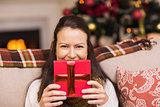 Pretty brunette woman holding christmas gift