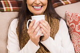 Mid section of a brunette enjoying a hot drink at christmas