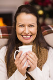 Smiling brunette enjoying a hot drink at christmas