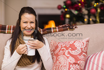 Smiling brunette enjoying hot chocolate
