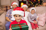 Smiling son holding gift in front of his family