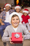 Festive son holding gift in front of his family