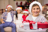 Festive son holding pile of gifts with his family behind