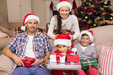 Pretty family posing with gifts during christmas