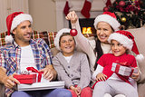 Festive family wearing santa hat on the couch
