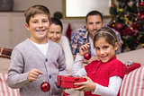 Smiling brother and sister holding gift and baubles