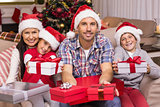 Festive family on the couch offering gifts