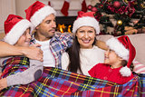Festive family in santa hat hugging under the cover