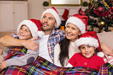 Happy family in santa hat hugging under the cover