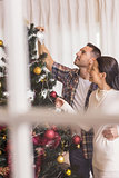 Love couple decorating the christmas tree together