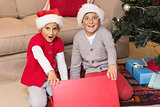 Astonished brother and sister opening a gift