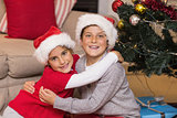 Smiling brother and sister hugging near the christmas tree