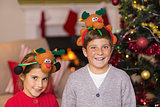 Happy brother and sister in headband near christmas tree