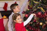 Brother and sister decorating the christmas tree together
