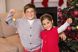 Happy brother and sister holding baubles