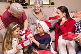 Multi generation family exchanging presents on sofa