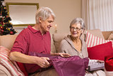 Senior couple opening a christmas present on sofa
