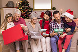Multi generation family opening gifts on sofa