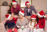 Happy extended family in santa hat holding gifts