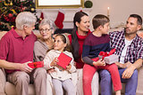Multi generation family holding presents on sofa