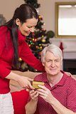Happy mother offering gift to grandfather