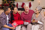 Smiling family holding gift on sofa