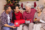 Smiling family holding present on sofa