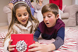 Surprised brother and sister lying opening gift