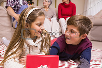 Smiling brother and sister lying and opening gift