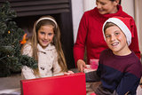 Portrait of son opening gift with his family
