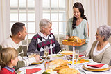 Woman holding turkey roast with family at dining table