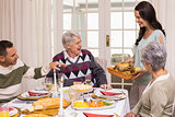 Woman holding turkey roast with family at christmas