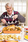 Portrait of a grandfather carving roast turkey at christmas