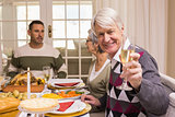 Smiling grandfather toasting at camera in front of his family