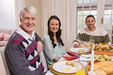 Cheerful family looking at camera during christmas dinner