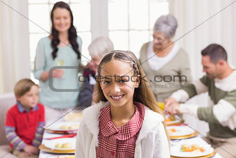 Portrait of girl smiling at camera in front of her family