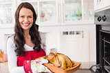 Smiling woman holding roast turkey