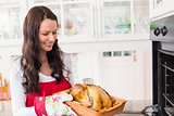 Happy woman holding roast turkey