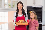 Surprised mother and daughter posing with roast turkey