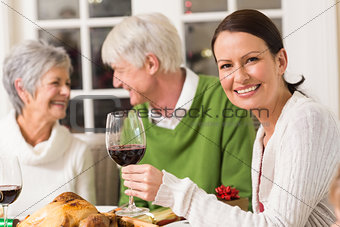 Portrait of woman toasting at camera during christmas dinner
