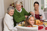 Smiling grandfather carving chicken during christmas dinner