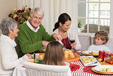 Happy grandfather carving chicken during christmas dinner